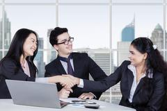 Female workers shaking hands closing a deal - stock photo