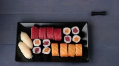Sushi set nigiri and rolls on black plate served with chopsticks, soy sauce - stock footage