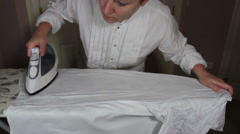 Obsessed woman frantically ironing a white shirt with a steam iron on a ironi Stock Footage