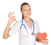 Woman intern holding paper heart in her hand and showing sign of okay - stock photo