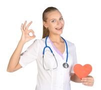 Woman intern holding paper heart in her hand and showing sign of okay Stock Photos