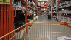 Shopping cart moving through the aisles of a big box hardware store - stock footage