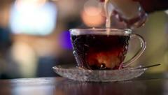 Pouring milk into hot black tea in cafe Stock Footage
