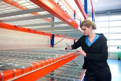 Young business woman writing on clipboard in warehouse - stock photo