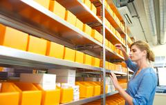 Portrait of a female worker organizing boxes on shelves - stock photo