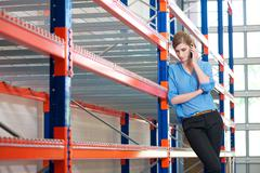 Confident business woman  on cellphone in warehouse - stock photo