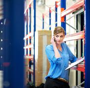 Female logistics employee on the phone and checking inventory - stock photo