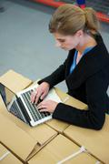 Business woman typing on laptop in warehouse - stock photo