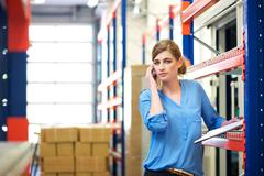 Female logistics worker on mobile phone in warehouse - stock photo