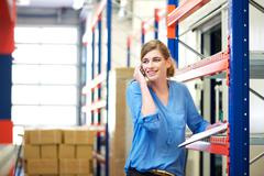 Female logistics worker controlling stock and talking on cellphone in warehou - stock photo