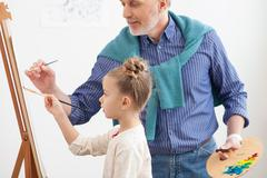 Talented old painter and his little grandchild - stock photo