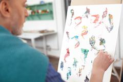 Talented mature painter is drawing a picture - stock photo