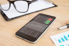 Phone and business stock application on work desk Stock Photos