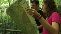 Hiking Couple Looking At Trail Map In Woods Stock Footage