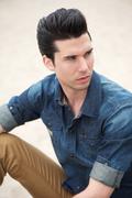 Male fashion model sitting outdoors - stock photo