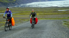 Cyclists riding on a background of a glacier Skaftafellsjokull. Iceland Stock Footage