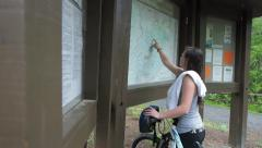 Girl With Mountain Bike Looking At Trail Map Stock Footage