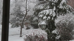 Snowy winter scene shot through home window Stock Footage