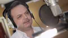 Portrait of man sing in headphones in front of microphone. Studio. Head movement Stock Footage