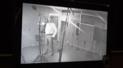 Man in shirt sing in studio in front of microphone. Surveillance camera view Stock Footage