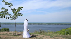 Bride with wedding bouquet stands near the river - stock footage