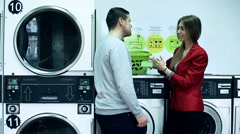 Young couple meeting and talking in public laundry - stock footage