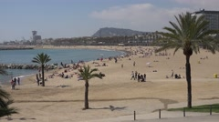 4K Tourist people relax sandy beach Barceloneta old port Barcelona emblem day Stock Footage