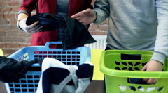 Couple folding clothes in laundry Stock Footage