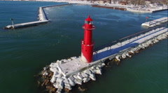 Stunning aerial rotation view of red lighthouse in icy harbor - stock footage