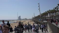4K Crowded beach pedestrian people walk promenade Barceloneta Barcelona icon day Stock Footage