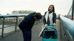 Family talking and walking with baby on bridge in city Stock Footage