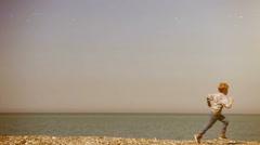 Beautiful minimalistic footage: a boy runs along the sea's shore Stock Footage