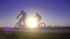 Bright saturated footage of two cyclists riding in one direction at sunset Stock Footage