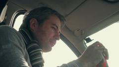 Handsome man wearing scarf drinks coffee  in his car in the morning. Slow motion Stock Footage