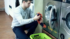 Young man taking clothes out of washing machine in public laundry Stock Footage