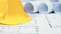 Hard hat and architectural drawings Stock Footage