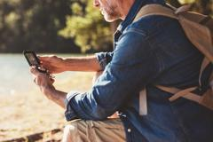 Hiker searching direction with a compass - stock photo