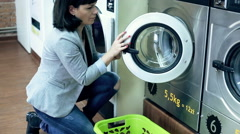 Young woman taking clothes out of washing machine in public laundry Stock Footage