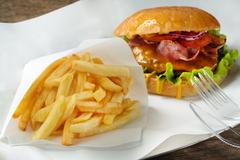 Burger, fries and fork with knife on paper - stock photo