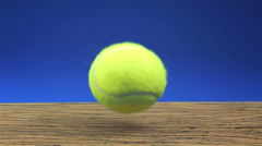 Tennisball bouncing on wood with blue background Stock Footage