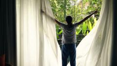 Young woman unveil curtains and looking on the garden, super slow motion Stock Footage