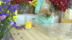 Flower shop, florist arranging mums bouquet, wrapping cellophane around bouquet - stock footage