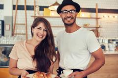 Couple with food and drink at coffee shop - stock photo
