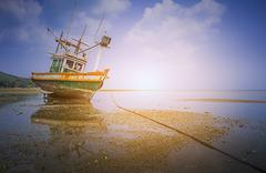 Small fishing vessels on the beach at dawn - stock photo
