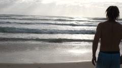 Single male walking towards the ocean Stock Footage