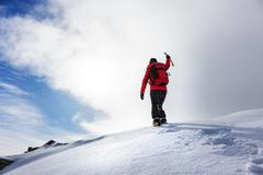 Mountaineer reaching the summit of a snowy peak in winter season. - stock photo