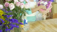 Flower shop, florist arranging bouquet, spraying water on the bouquet Stock Footage