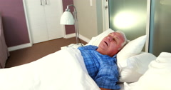 Senior woman blocking out his husband snoring Stock Footage