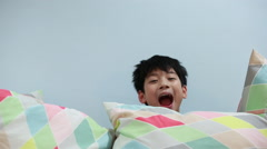 Little Asian child play hide and seek on the sofa bed - stock footage