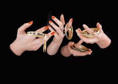 Two women's hands with golden bracelets Stock Photos